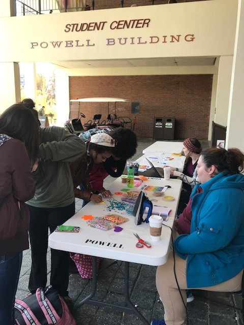 Students creating a keychain outside Powell Corner
