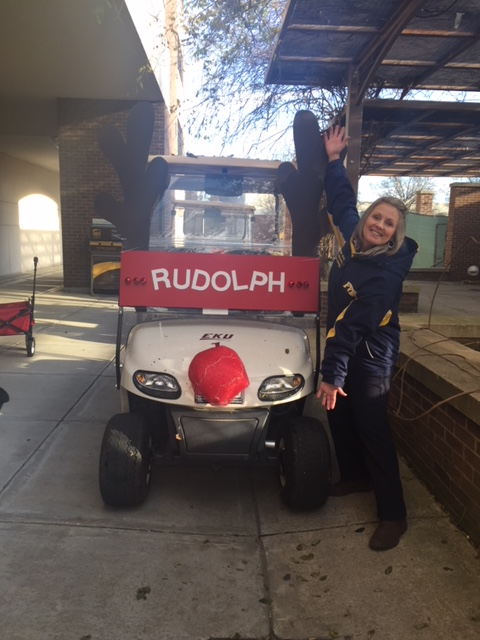 The costume designer posing with Rudolph, the red-nosed Golf Cart