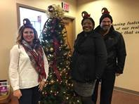 Housing & Residence Life Office Staff pose before the Office Tree, dressed as Caroling Elves.